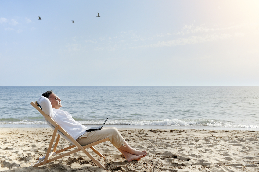 A man works on his laptop from the beach