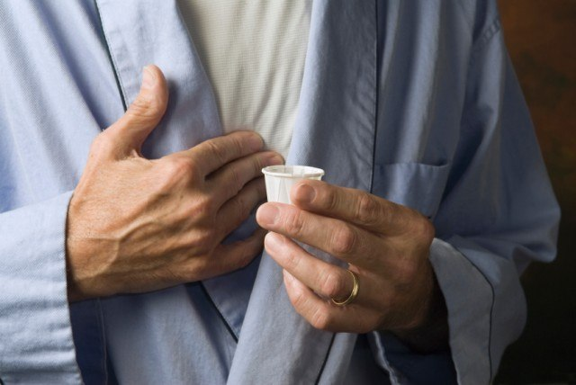 man holding his chest with medication in hand