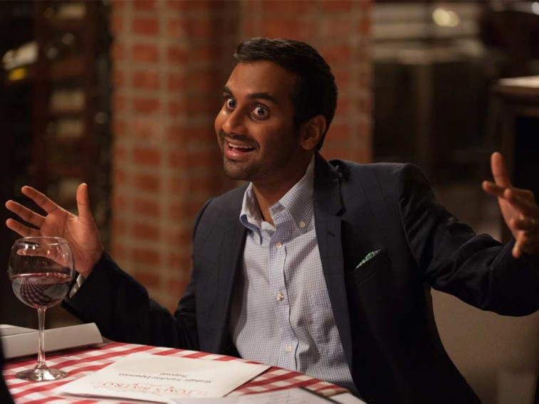 Aziz Ansari sits in a restaurant at a table with a glass of wine in Master of None