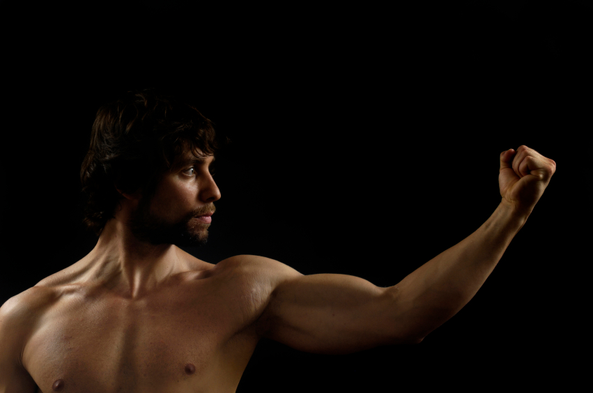 shirtless man flexing arm and posing