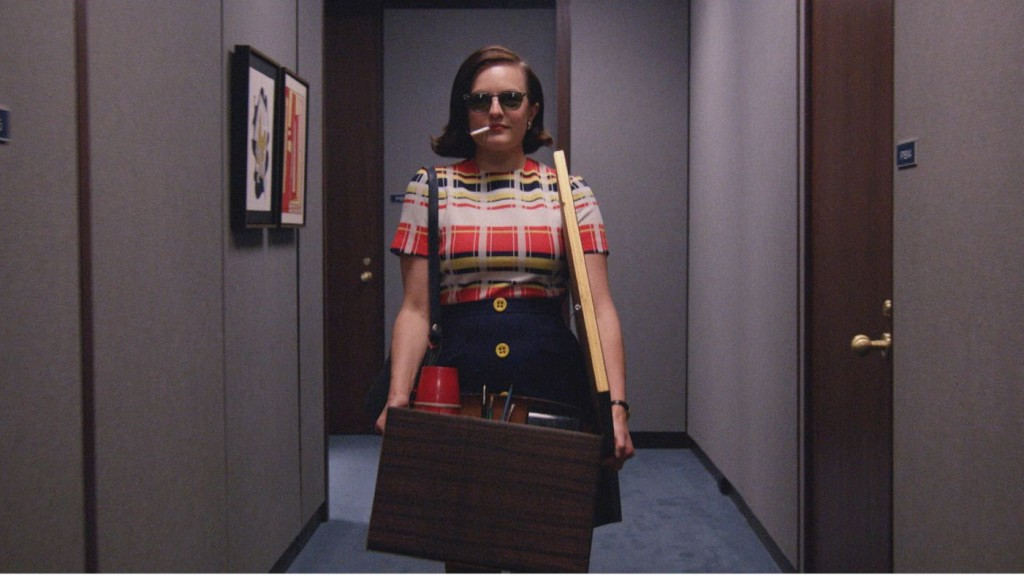 Peggy Olsen is walking down a hallway with a box of her things.