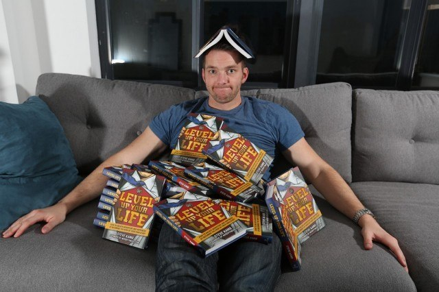 Steve Kamb of Nerd Fitness covered in a pile of books on a couch