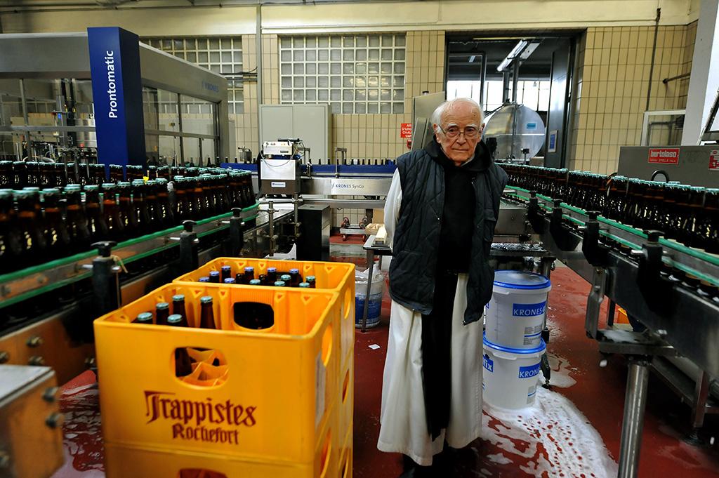 Trappist Monk overseeing beer bottling in Belgium