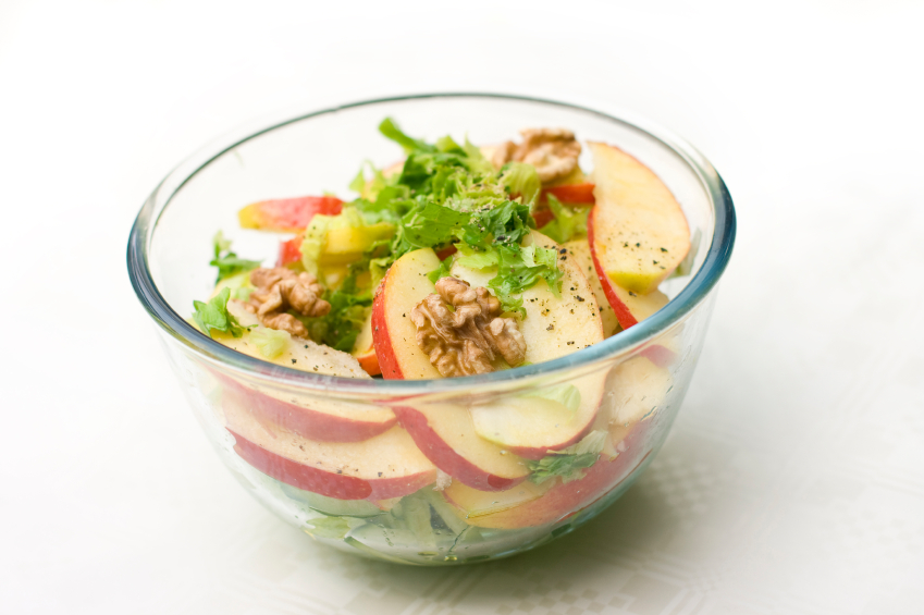 clear glass bowl with apple, walnut, and frisee salad