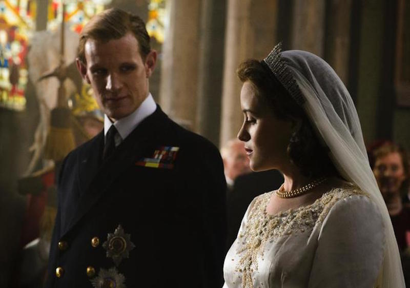 Claire Foy wears a wedding dress and stands next to her husband to be in the Crown