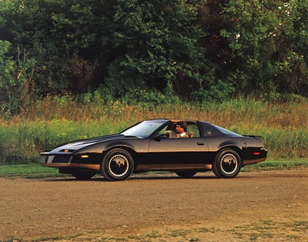 A black 1982 Pontiac Trans Am drives down a dirt road