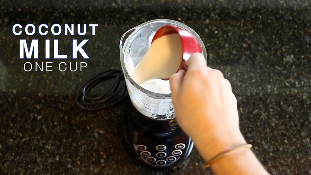 adding coconut milk to a blender with ice