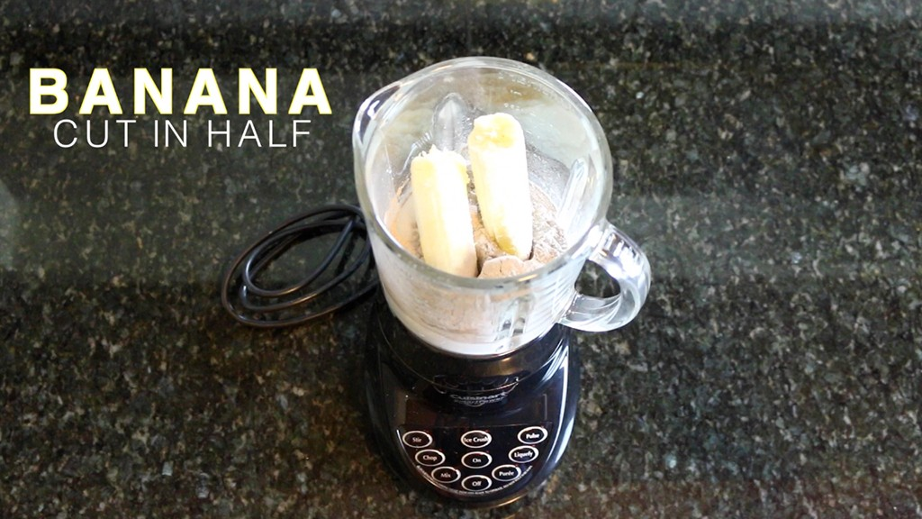 adding a halved banana to a blender for a protein shake