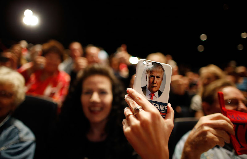 a Donald Trump supporter holds a phone with Trump's face on it at a rally