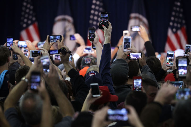 crowds wait with their phones to see Donald Trump at a rally