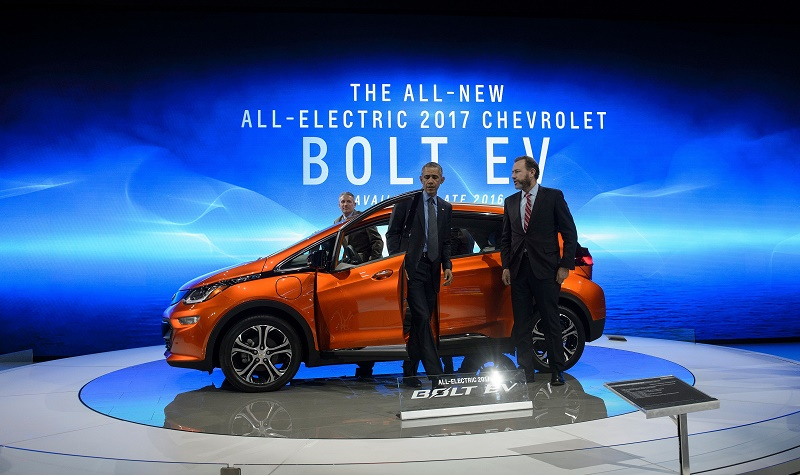 Patrick Foley, Bolt EV specialist, and Dan Ammann, President of General Motors, wait while US President Barack Obama gets out of a Chevey Bolt EV at the North American International Auto Show January 20, 2016 in Detroit, Michigan.