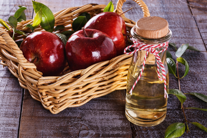 Apple cider vinegar with apples in a basket