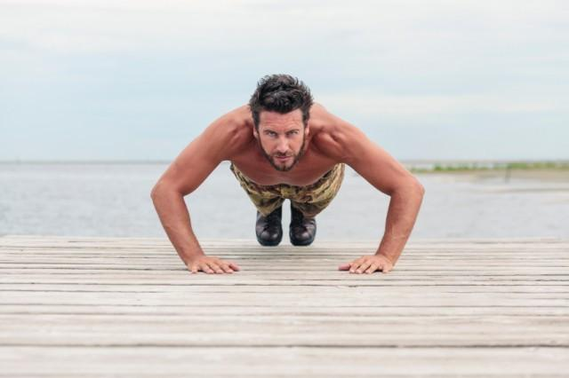 man performing push-ups on a dock outside