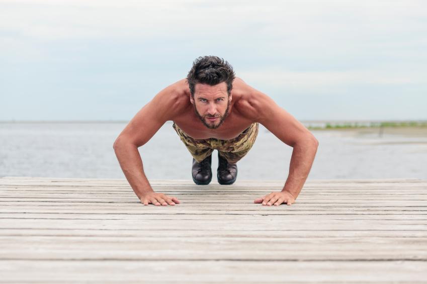 man doing push ups at a beach