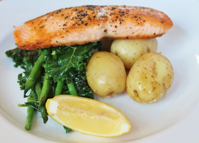 dish of scottish salmon potatoes served with lemon and greens
