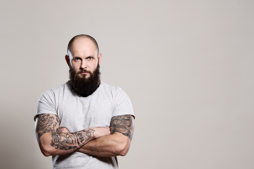 A tattooed man with a beard who's probably feeling it in the paycheck