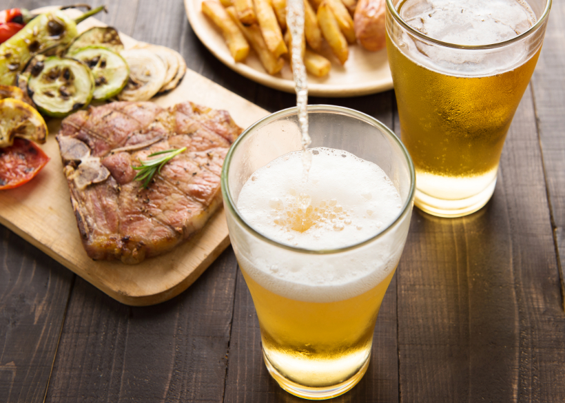 two beer glasses, one bing poured, with steak and fries