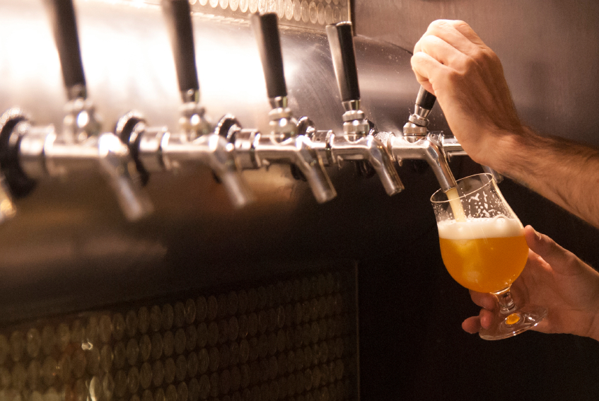 man pouring beer from a tap in the wall