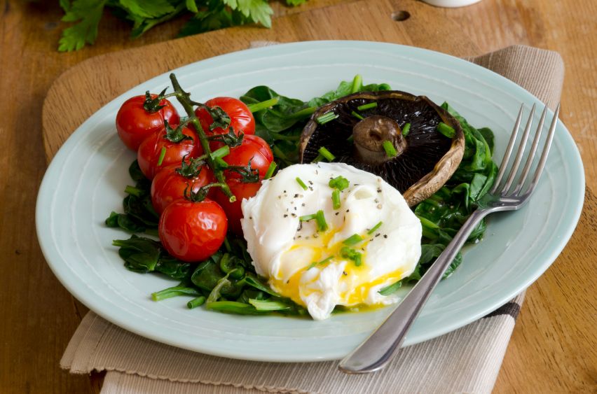 healthy breakfast with poached eggs served over spinach and mushrooms