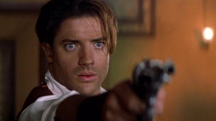 Brendan Fraser is pointing a gun in The Mummy