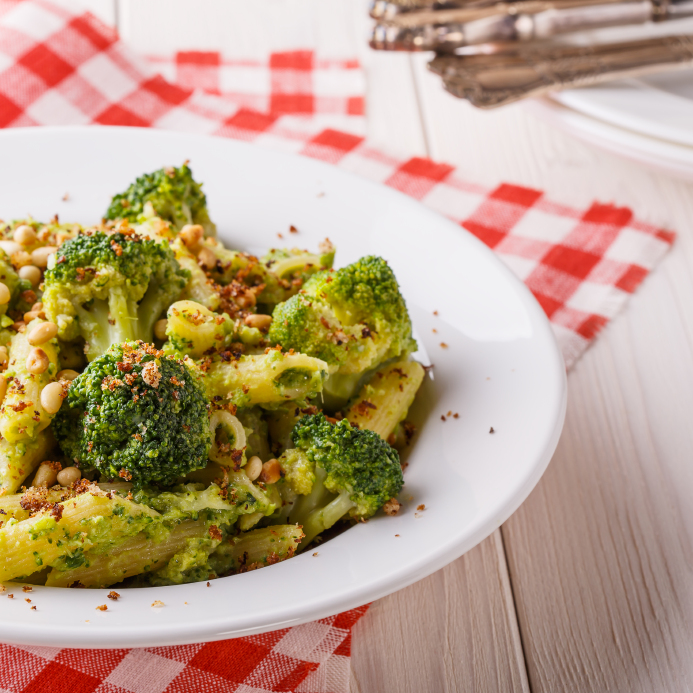 bowl of broccoli pasta with a checkered palcemat