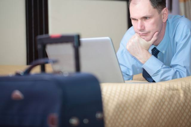 man on computer in a hotel room