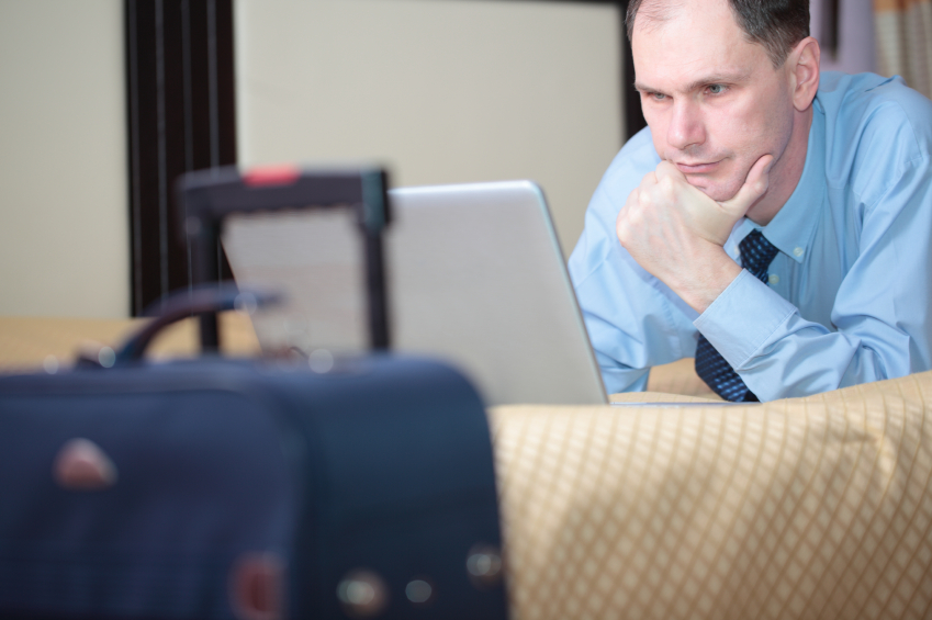Businessman using laptop on bed