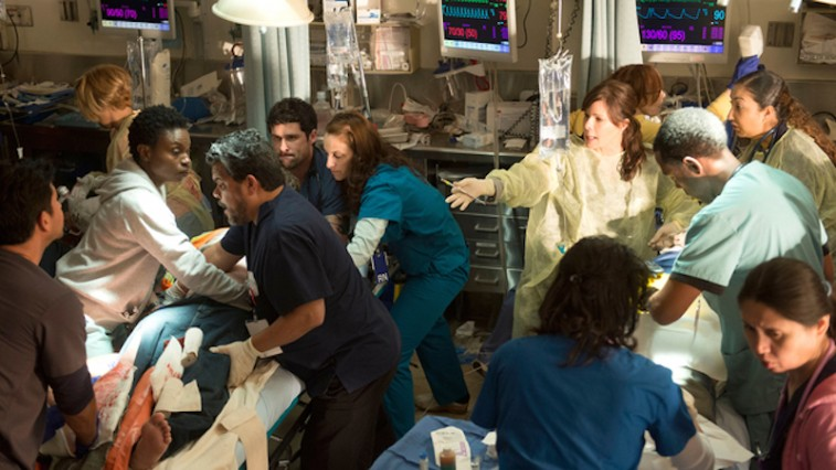 A group of doctors and nurses huddle around a patient in a scene from Code Black