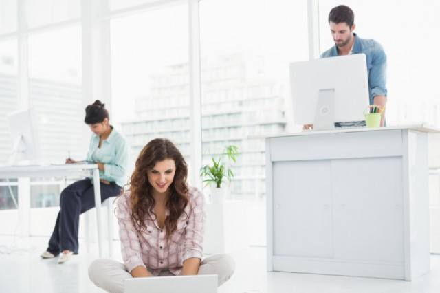 man at standing desk, woman on floor working on laptop