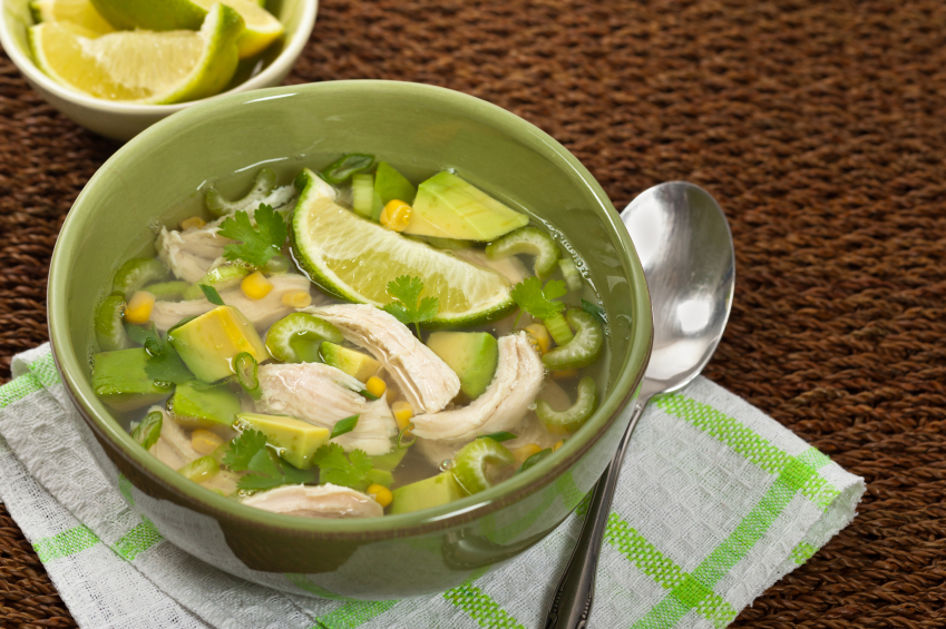 bowl of chicken and avocado soup with corn, cilantro, and lime