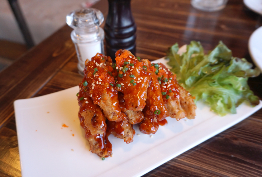 fancy plate of chicken withs with Korean chile sauce and sesame seeds