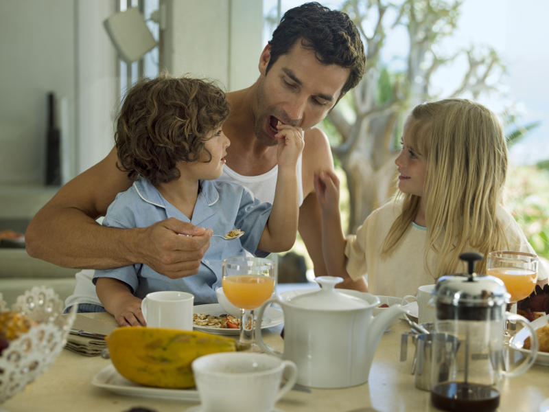 Children feeding their father breakfast