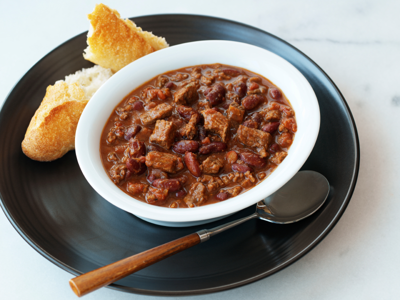 white bowl filled with cili con carne on a platter with a side of bread