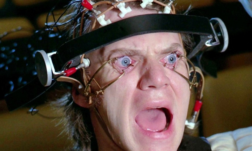 Alex is in headgear that is keeping his eyes open and he's yelling in A Clockwork Orange.