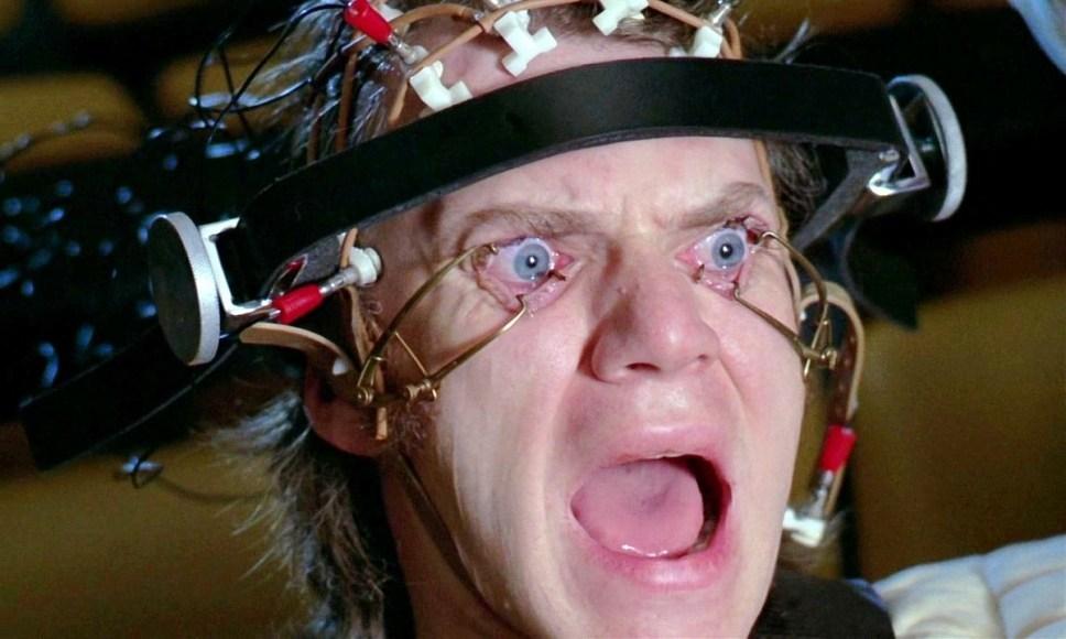Alex is in headgear that is keepin his eyes open and he's yelling in Clockwork Orange.