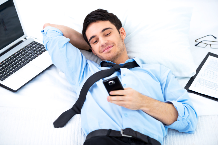 young business man lying and using smartphone