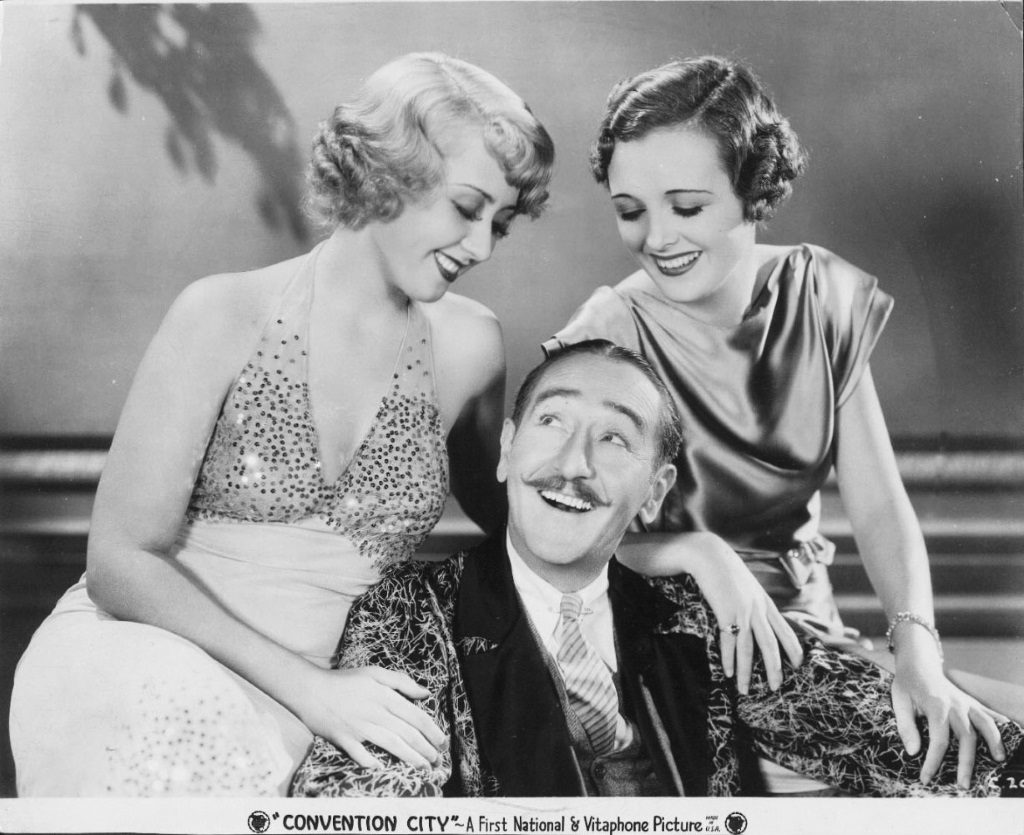 Joan Blondell, Adolphe Menjou, and Mary Astor looking at one another in fancy attire with their arms resting on one another in Convention City (1933)