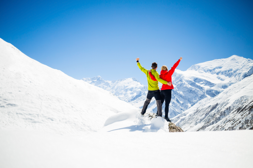 couple celebrating success on snowy mountain