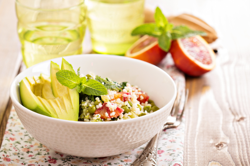 bowl of couscous with herbs and sliced avocado