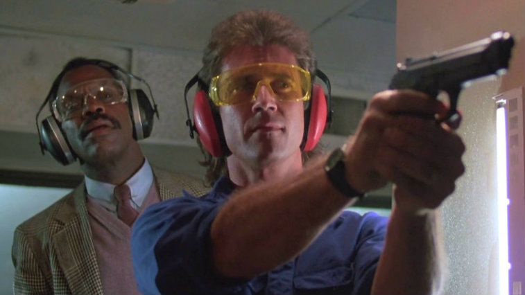 Mel Gibson is shooting a gun and Danny Glover is looking over his shoulder in Lethal Weapon.