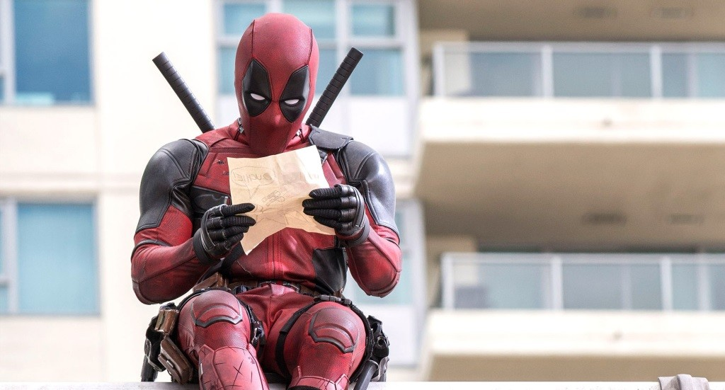 Deadpool looks at a piece of paper while in uniform