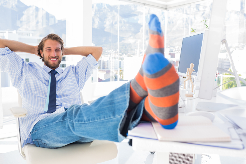 young man relaxing in an office with both feet on the desk