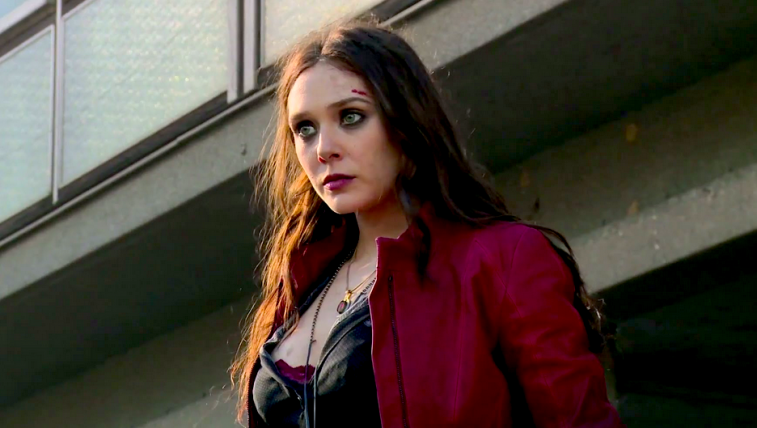 Elizabeth Olsen wears a red leather jacket and stands in front of a building in Captain America: Civil War