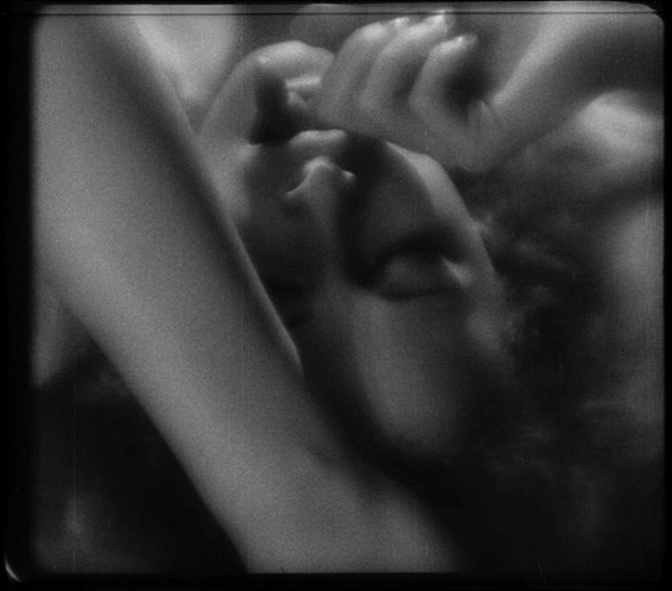 Hedy Lamarr star of Ecstasy (1933) upside down with her eyes closed and her finger in her mouth in black and white