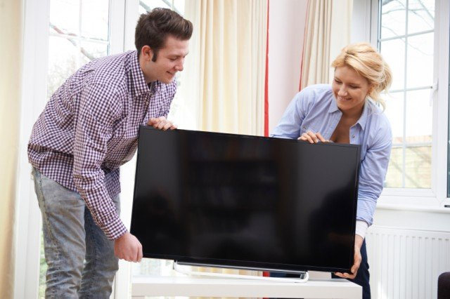 Couple moving a TV