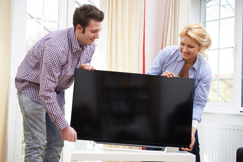 couple putting a new flatscreen TV in their living room