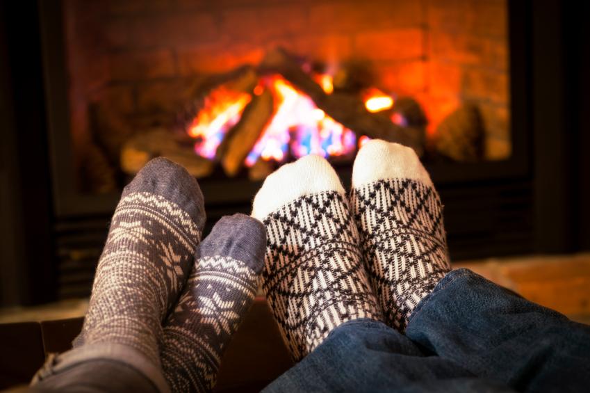 Couple warming feet in wool socks by fireplace