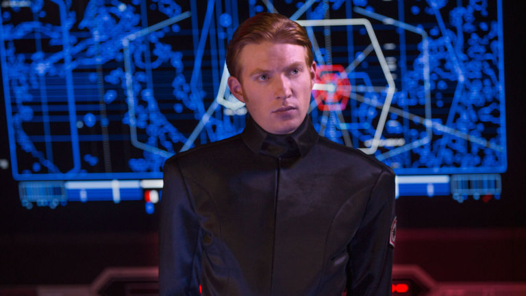 General Hux, looking off to the right, wearing a crisp officer's uniform in front of a blue digital readout
