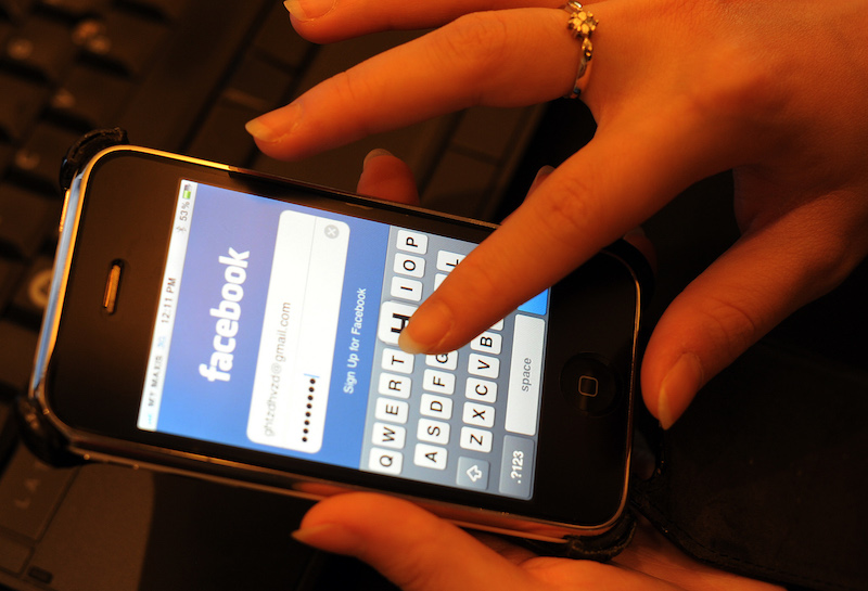 a hand typing in a password on the facebook app