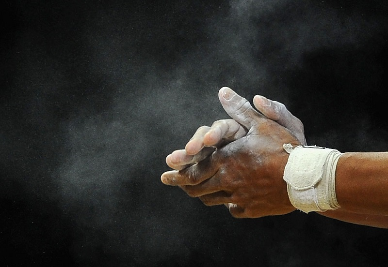 A man putting chalk on his hands